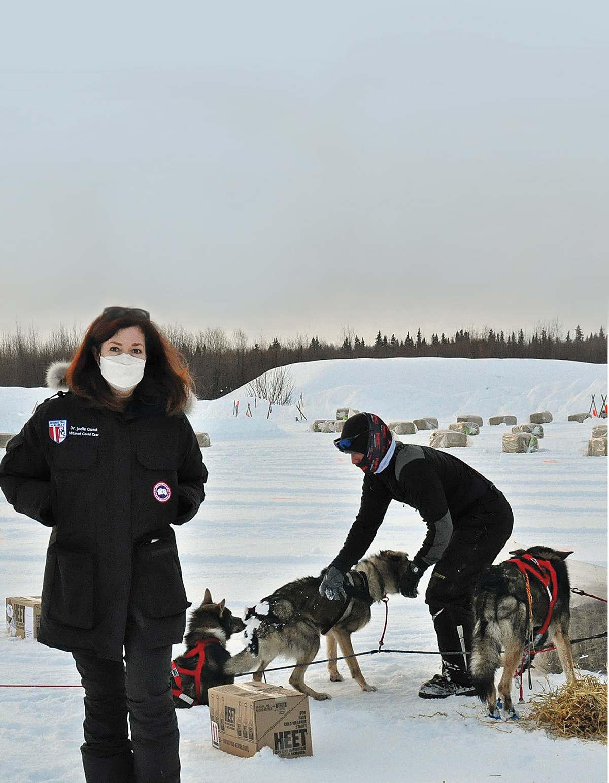 Emory researcher Dr. Jodi Guest stands in the snow, wearing a parka and face covering, surrounded by sled dogs and gear.